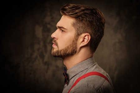 Jonge knappe man met een baard dragen bretels en poseren op een donkere achtergrond.