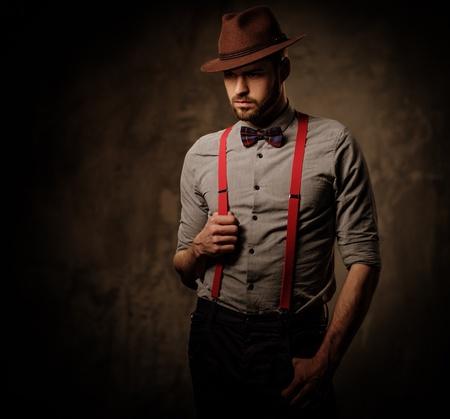 Serious altmodischen Mann mit Hut trägt Strapse und Fliege, auf dunklem Hintergrund aufwirft. Standard-Bild - 55455242