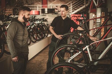자전거 가게에 관심이 고객에 게 새로운 자전거를 보여주는 세일즈 맨.