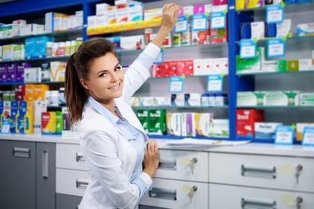 아름다운 약국에서 자신의 일을 젊은 여자 약사 미소. 스톡 콘텐츠