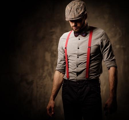 Serious ouderwetse man in tweed hoed dragen bretels en vlinderdas, die zich voordeed op een donkere achtergrond. Stockfoto