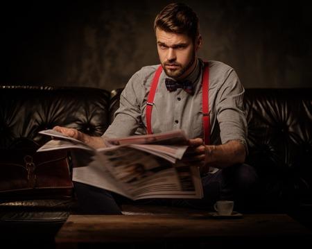 Jonge knappe ouderwetse bebaarde man met krantenzitting op comfortabele leerbank op donkere achtergrond. Stockfoto