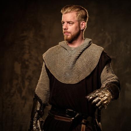 caballero medieval joven que presenta en fondo oscuro. Foto de archivo