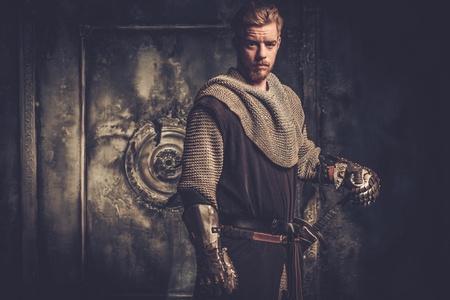 caballero medieval joven que se coloca en el fondo oscuro. Foto de archivo