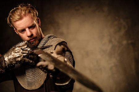 Young medieval knight posing on dark background. Stock Photo - 55961889