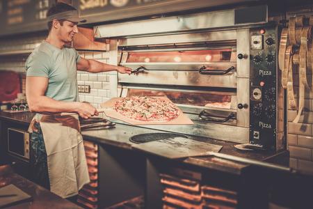 피자 가게에서 주방에서 피자를 만드는 잘 생긴 pizzaiolo.