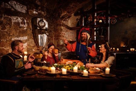중세 사람들은 먹고 고대의 성 부엌 인테리어에 마신다. 스톡 콘텐츠