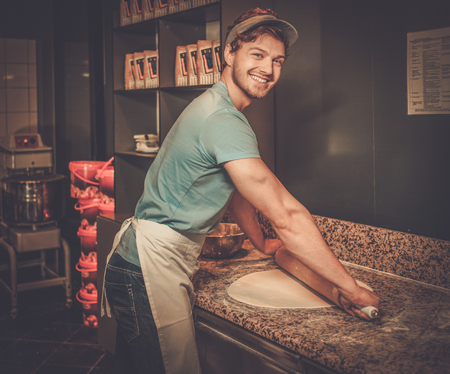 Handsome pizzaiolo rolling dough with rolling-pin.
