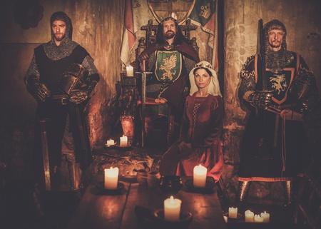 Mittelalterliche König mit seiner Königin und Ritter auf Wache im alten Schlossinnenraum.