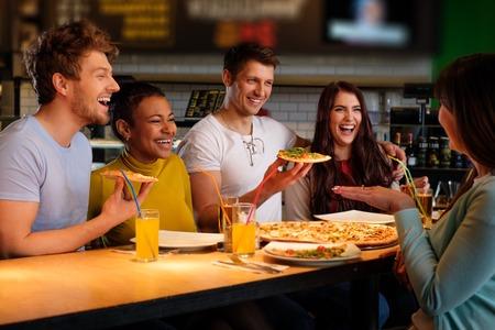 Cheerful multiracial friends having fun eating in pizzeria.