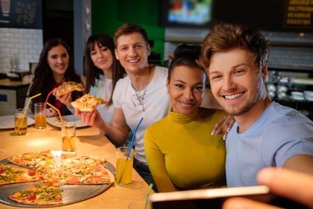 Vrolijke multiraciale vrienden nemen selfie in pizzeria.