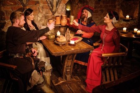 중세 사람들이 고대 성 선술집에서 먹고 마 십니다. 스톡 콘텐츠