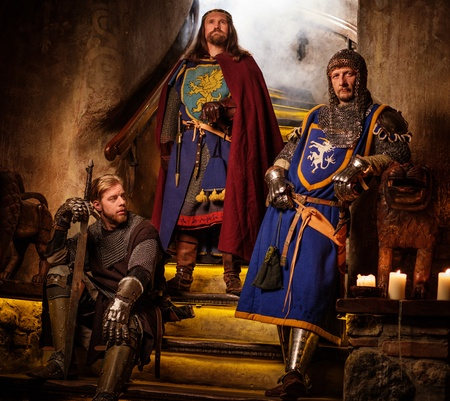 Medieval king with his  knights in ancient castle interior. Stock Photo