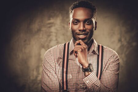 Stijlvolle jonge zwarte man met bretels die zich voordeed op een donkere achtergrond. Stockfoto