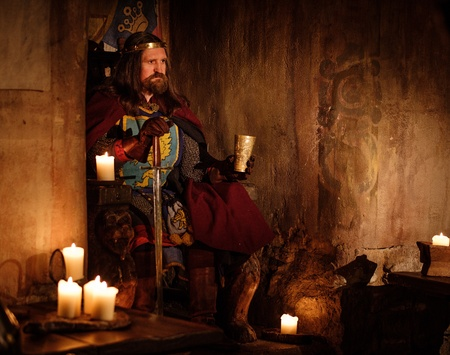 Old medieval king with goblet of wine on the throne in ancient castle interior.