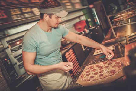 pizzaiolo Handsome faire pizza à la cuisine dans une pizzeria.