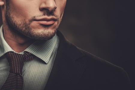 Serious goed geklede Spaanse man die zich voordeed op een donkere achtergrond.