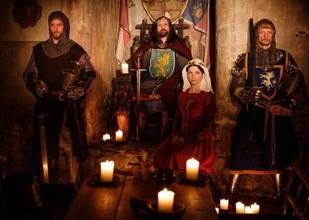 Middeleeuwse koning met zijn koningin en ridders op wacht in het oude kasteel interieur.