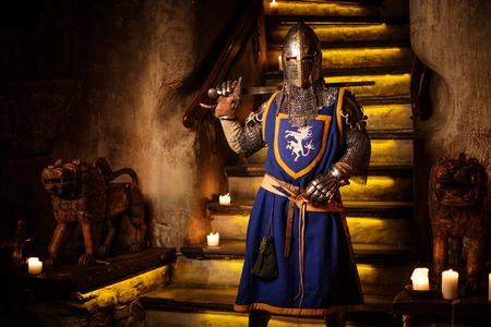 Middeleeuwse ridder op wacht in het oude kasteel interieur. Stockfoto