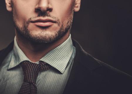Uomo ispanico ben vestito serio che posa sul fondo scuro. Archivio Fotografico