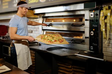 pizzaiolo hermoso que hace pizza en la cocina de una pizzería.