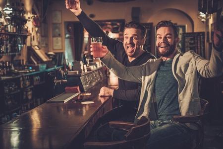 Vrolijke oude vrienden plezier kijken naar een voetbalwedstrijd op tv en het drinken van bier van het vat op bar in pub.