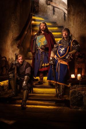 roi médiéval avec ses chevaliers dans l'ancien intérieur du château.