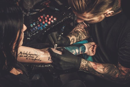 Professional tattoo artist makes a tattoo on a young girl's hand. Standard-Bild