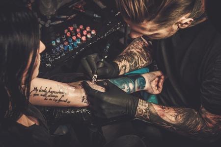tatuatore professionista fa un tatuaggio sulla mano di una giovane ragazza.