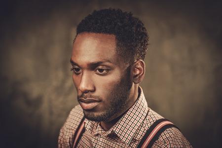 Stijlvolle jonge zwarte man met bretels die zich voordeed op een donkere achtergrond.