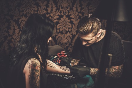 Professionele tattoo kunstenaar maakt een tatoeage op de hand van een jong meisje.