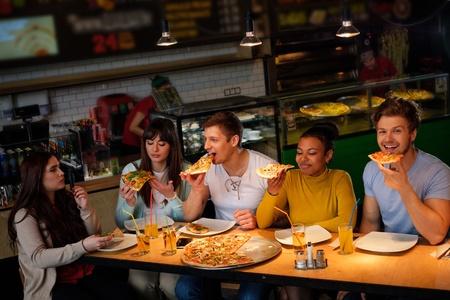 Vrolijke multiraciale vrienden die pret hebben die pizza in pizzeria eten.