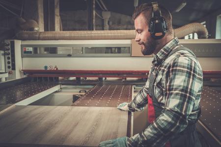 大工は大工のワーク ショップで木の板に動作します。 写真素材