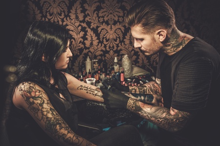Professional tattoo artist makes a tattoo on a young girls hand. Banco de Imagens