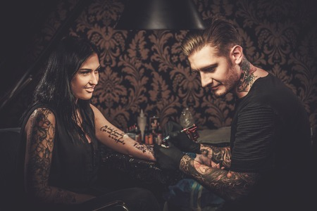 Professional tattoo artist makes a tattoo on a young girl's hand. Banque d'images