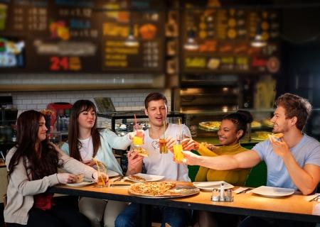 Vrolijke multiraciale vrienden plezier pizza eten in pizzeria.