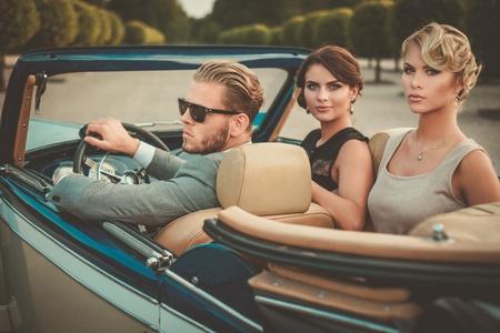 Riches amis dans un cabriolet classique Banque d'images - 57501723