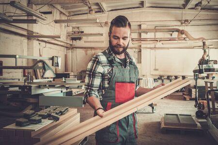 Carpenter doing his job in carpentry workshop. Reklamní fotografie