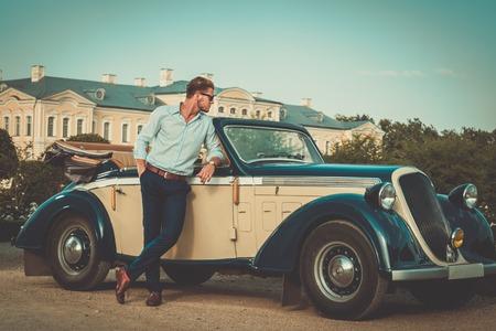 Zelfverzekerd rijke jonge man in de buurt van klassieke cabriolet Stockfoto