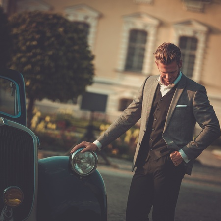 Confident wealthy young man with newspaper near classic convertible Фото со стока