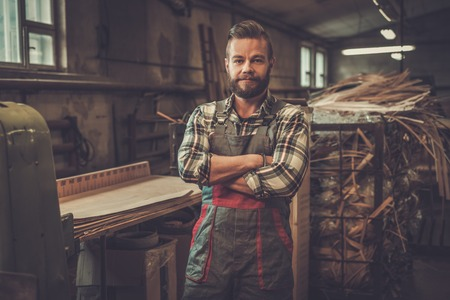 Carpenter posing on his workplace in carpentry workshop. Standard-Bild
