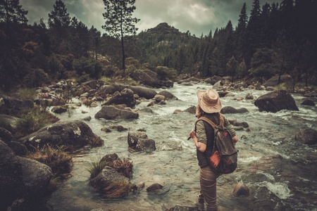 Beautiful woman hiker enjoying amazing landscapes near wild mountain river. Stock Photo