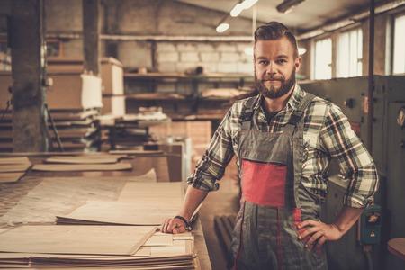 Carpenter posing on his workplace in carpentry workshop. Standard-Bild