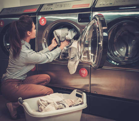 Beautiful woman doing laundry at laundromat shop Banco de Imagens