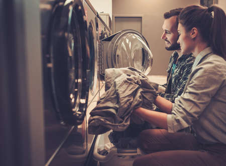 Young cheerful couple doing laundry together at laundromat shop