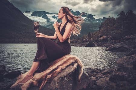Nordic Göttin in rituellen Gewand mit Habicht in der Nähe von Wild Bergsee in Innerdalen-Tal, Norwegen.