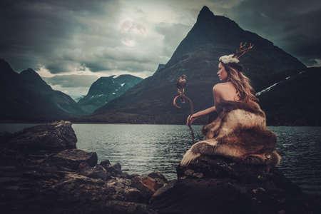 diosa nórdica en la ropa ritual con halcón cerca del lago de montaña salvaje en Innerdalen valle, Noruega.