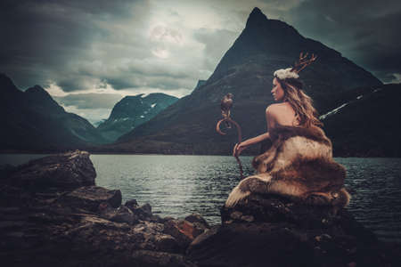 Nordic goddess in ritual garment with hawk near wild mountain lake in Innerdalen valley, Norway. Stockfoto
