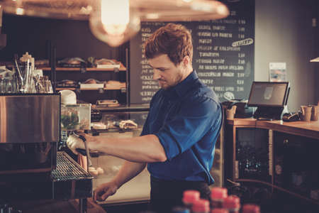 Handsome barista preparing cup of coffee for customer in coffee shop. Reklamní fotografie - 61278256