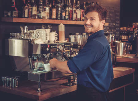Handsome barista preparing cup of coffee for customer in coffee shop. Imagens - 61278257